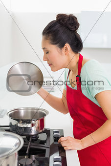 Side view of a young woman preparing food in kitchen