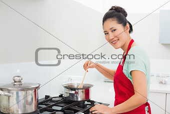 Side view portrait of a woman preparing food in kitchen