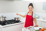 Smiling woman with recipe book preparing food in kitchen