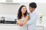 Smiling man embracing woman from behind in kitchen