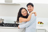 Young man embracing woman in kitchen