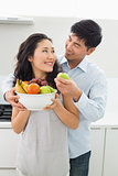 Young couple holding bowl full of fruit in kitchen
