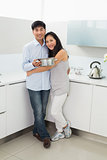 Portrait of a young woman embracing man in kitchen