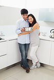 Full length of a woman embracing man in kitchen