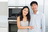 Portrait of a smiling young couple in the kitchen