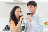 Loving young couple drinking red wine in kitchen