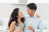 Loving young couple with wine glasses in kitchen