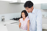 Smiling father and daughter using laptop in kitchen