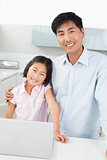 Smiling father and young daughter with laptop in kitchen