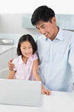 Smiling father with daughter using laptop in kitchen