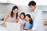 Shocked family of four using laptop in kitchen