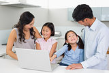 Happy family of four using laptop in kitchen