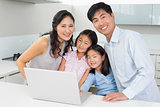 Portrait of a happy family of four with laptop in kitchen