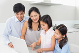 Family of four using laptop in kitchen