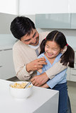 Cheerful father and daughter having cereals in kitchen
