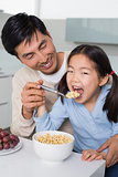Father with young daughter having cereals in kitchen