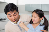 Young daughter feeding cereals to father in kitchen