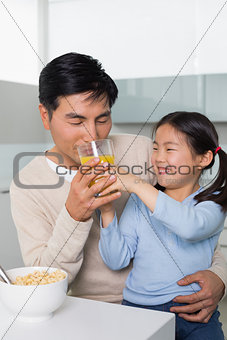 Father with daughter having breakfast in kitchen