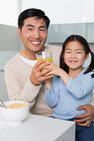 Happy father with daughter having breakfast in kitchen