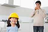Cute girl in hard hat with father drinking orange juice in kitchen