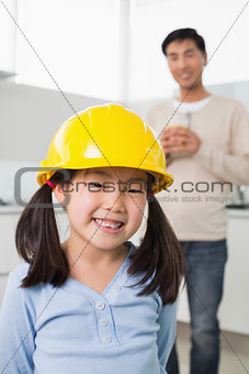Cute girl in yellow hard hat with father in background