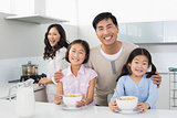 Family of four having breakfast in the kitchen