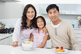 Couple with a daughter having breakfast in kitchen