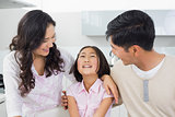 Smiling couple with a cheerful daughter in kitchen