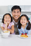 Smiling man with two daughters having breakfast in kitchen