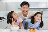 Smiling man with happy two daughters having breakfast in kitchen