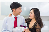 Couple with gift box in the kitchen at home