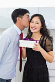 Young man kissing a woman as he gives her a gift box