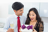 Shocked woman opening a gift box by man with champagne