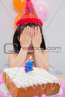 Girl covering her face at the birthday party