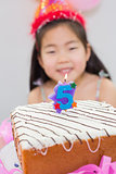 Blurred little girl with lit candle on birthday cake