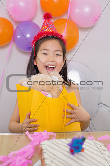 Cheerful surprised little girl at her birthday party