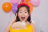 Shocked little girl with gift at her birthday party