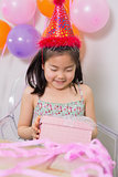 Little girl with gift box at her birthday party