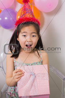 Shocked girl opening gift box at her birthday party