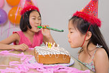 Girls blowing noisemaker and birthday candles