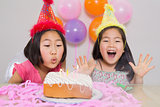 Young girls blowing cake at a birthday part