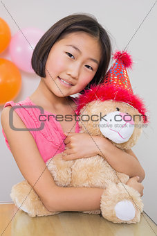 Cute little girl hugging soft toy at a birthday party