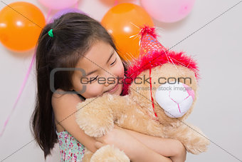 Cute girl hugging soft toy at a birthday party