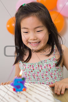 Cute girl looking at cake at her birthday party
