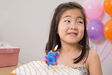 Cute little girl with cake at her birthday party