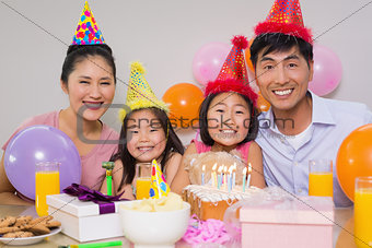 Family of four with cake and gifts at a birthday party