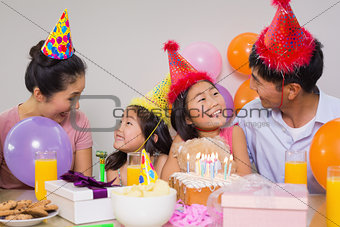 Family with cake and gifts at a birthday party