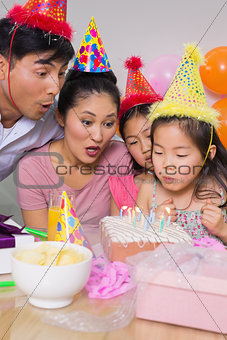 Family blowing cake at a birthday party