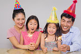 Cheerful family of four playing with firecrackers
