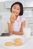 Smiling young girl enjoying cookies and milk